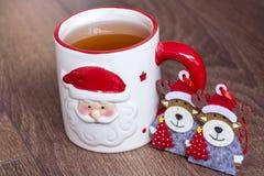 在一个红色杯子的热的冬天茶有圣诞节装饰鹿的 免版税库存照片