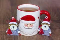 在一个红色杯子的热的冬天茶有圣诞节装饰鹿的 图库摄影