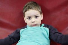 在一个红色沙发的孩子 免版税库存图片