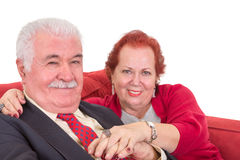 在一个红色沙发的富感情的资深夫妇 库存照片