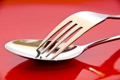 在一个红色牌照的叉子和匙子 免版税库存图片
