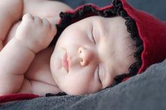在一个红色盖帽的新出生的婴孩特写镜头 beauti的特写镜头画象 免版税库存图片