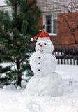 在一个红色盖帽的雪人有红萝卜鼻子的 库存图片