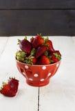 在一个红色碗的草莓有在豌豆的一个样式的在一张白色桌上 库存照片