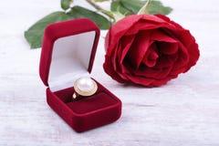 在一个红色礼物盒的金黄珍珠圆环和在白色木背景上升了 免版税库存照片
