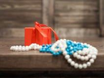 在一个红色箱子和珍珠,绿松石小珠的一件礼物从桌的边缘垂悬 库存图片