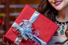 在一个红色箱子的一件礼物有一把发光的弓的在甜甜地微笑女孩的手上 图库摄影