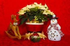 在一个红色篮子的一品红与蜡烛、雪人和驯鹿 免版税库存照片