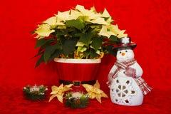 在一个红色篮子的一品红与蜡烛和雪人 免版税库存图片