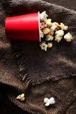 在一个红色纸板箱的新鲜的玉米花在木桌上,戏院 图库摄影
