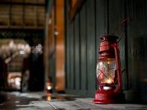 在一个红色老灯笼的射击焦点在黑暗的湿木地板机智 免版税库存图片