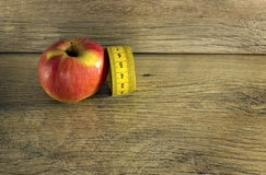 在一个红色苹果附近被包裹的测量的磁带 免版税库存照片