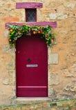 在一个红色葡萄酒门的手工制造花圈 免版税图库摄影