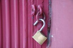 在一个红色金属门的开锁的黄铜挂锁 库存图片