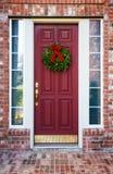 在一个红色门的圣诞节花圈 免版税库存图片