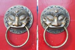 在一个红色门的金黄色的中国通道门环 免版税库存照片