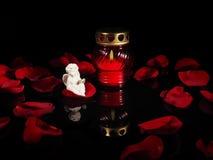 在一个红色玻璃烛台的灼烧的蜡烛 免版税库存照片