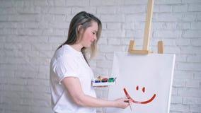 在一个纯稚样式的愉快的面带笑容,女孩艺术家绘了在一块白色帆布的微笑 股票录像