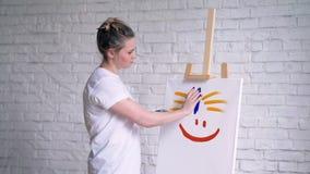 在一个纯稚样式的愉快的面带笑容,女孩艺术家绘了在一块白色帆布的微笑 股票视频