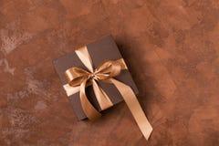 在一个纸箱的一件礼物用一缎带和一把弓装饰在棕色背景 欢乐概念 平的布局 库存图片