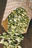 在一个纸袋的干绿色南瓜籽 免版税库存图片