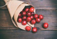 在一个纸袋的成熟和水多的红色樱桃 免版税库存图片