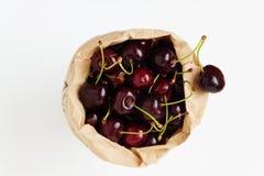 在一个纸袋的新鲜的樱桃莓果,隔绝在一白色backgro 图库摄影