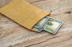 在一个纸袋的美元在木背景 免版税图库摄影