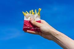 在一个纸袋的酥脆炸薯条在蓝天背景的一只男性手上 免版税库存照片