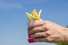 在一个纸袋的酥脆炸薯条在蓝天背景的一只男性手上 库存图片
