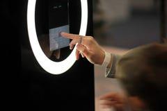 在一个终端的一个发光的数字式触摸屏上的妇女` s手拨的数字商城的 免版税图库摄影