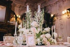 在一个经典样式的装饰的典雅的宴会桌在豪宅 用白花花束从玫瑰的装饰 免版税库存图片