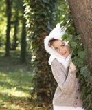 在一个结构树之后的美丽的女孩在森林里 免版税库存图片