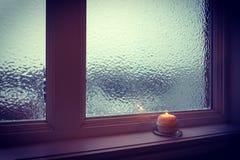 在一个结霜的窗口附近对光检查燃烧在微明下 库存图片
