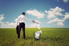 在一个绿色域的生意人投掷在垃圾的纸张 免版税库存照片