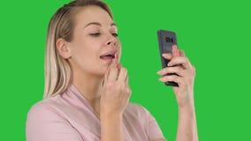 在一个绿色屏幕上的电话绘她的有红色口红的嘴唇并且看的美丽的年轻白肤金发的妇女 股票视频