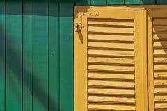 在一个绿色棚子的一个黄色窗口 库存照片