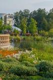 在一个绿色水多的公园、花和树中间的一个池塘与一个现代大厦和观察平台在绿色中 库存图片