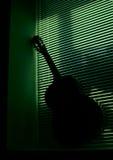在一个绿色背景的吉他 免版税库存照片