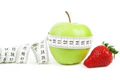 在一个绿色苹果和草莓附近被包裹的评定的磁带作为饮食的符号 免版税图库摄影