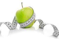 在一个绿色苹果附近被包裹的评定的磁带 图库摄影