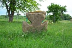 在一个绿色草甸的老石十字架 免版税图库摄影