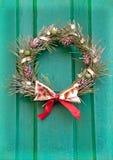 在一个绿色门的圣诞节花圈。 免版税库存照片