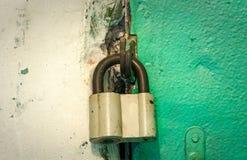在一个绿色门的锁着的老铁挂锁 库存照片