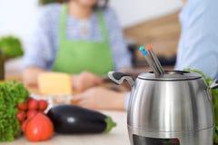 在一个罐的涮制菜肴在一起烹调的朋友背景,特写镜头 厨房内部和炊具 免版税库存照片