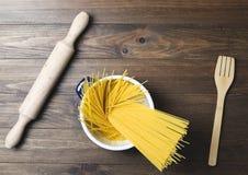 在一个罐里面的意粉在木桌上的一把木叉子旁边 免版税图库摄影