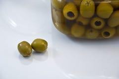 在一个罐头附近的橄榄在白色背景 免版税图库摄影