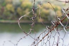 在一个网的铁丝网在河的背景,关闭上 库存图片