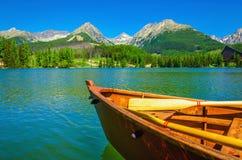 在一个美丽的山湖的木小船 免版税库存照片