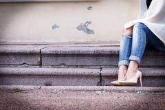 在一个美丽的桃子高跟鞋的女性腿有金子的引导 特写镜头 手改正了牛仔裤 库存照片